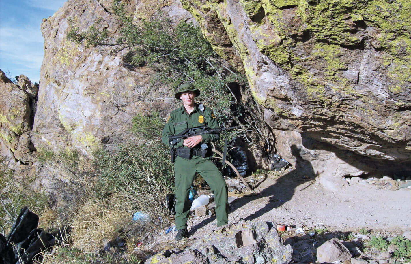 A young man in a green uniform stands on the edge of a desert cliff