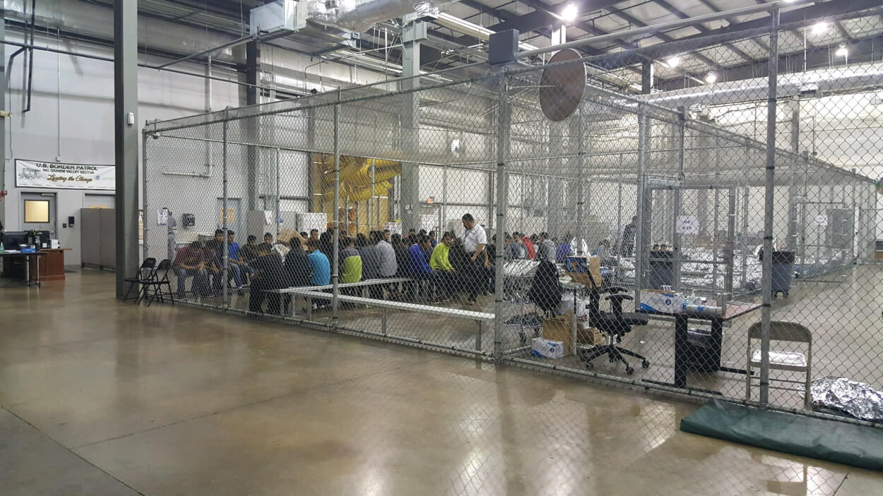 Groups of detainees sit at tables within a chainlink enclosure