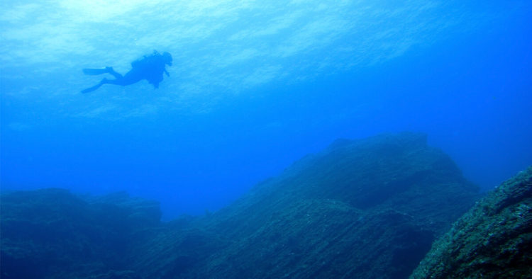 A scuba diver descends to the jagged edge of a rock beneath the deep blue sea