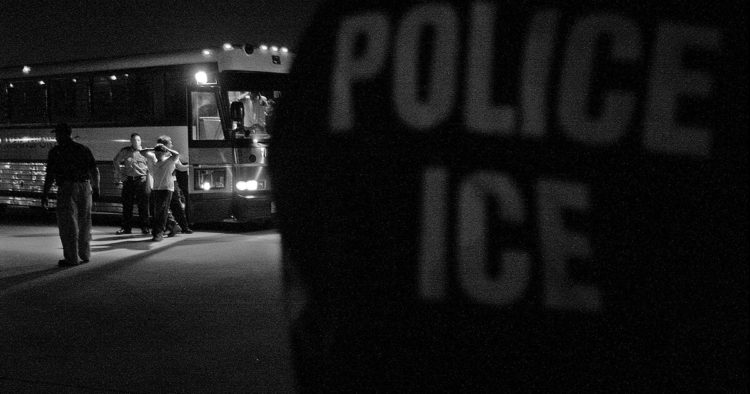 Black and white photo of ICE agents deporting migrants