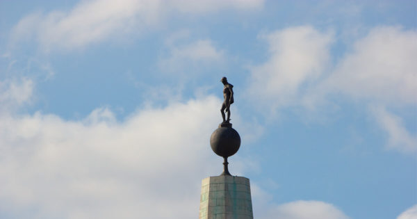 A picture of a statue of a man standing on a globe