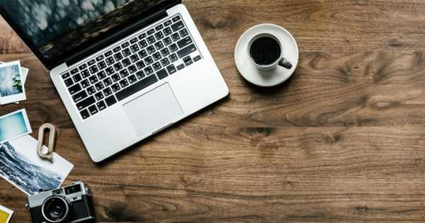 A laptop sits open on a rustic wooden table next to a coffee and an evocative travel photograph